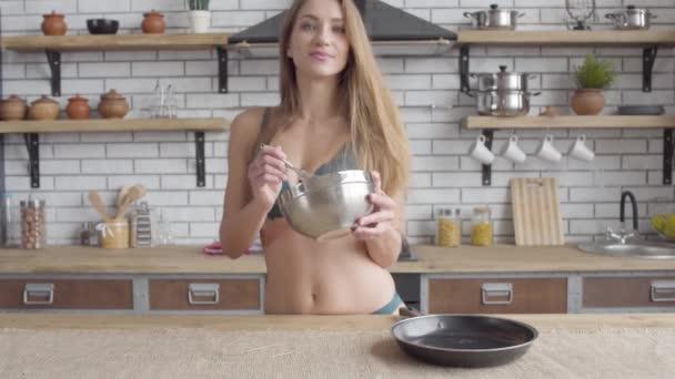 Portrét roztomilá mladá žena v prádlo kypřícího rozšleháme ve velké mísy stojící v kuchyni. Smyslná dívka vaření doma