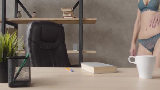 Velmi smyslná dívka v prádle sedí v černém koženém křesle poblíž police s nohama v černé boty na tabulky čtení knihy držení pera. Volný čas mladých krásné lonely Girl.