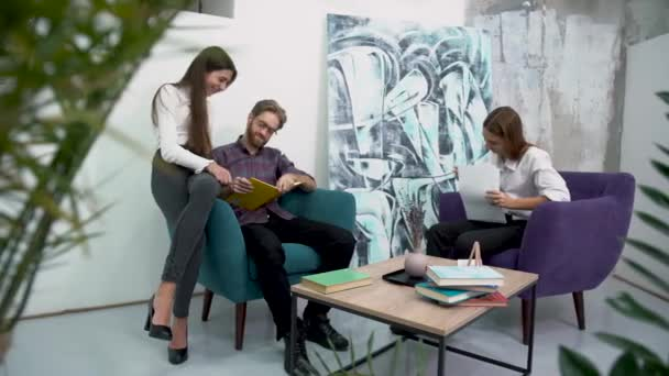 Bearded manager with glasses and two girls colleagues sitting in chairs discussing work plans in a relaxed atmosphere. Creative business team meeting in modern office.