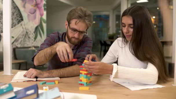Handsome bearded man with glasses and a cute girlfriend with long dark hair are building a tower of multi-colored wooden blocks while sitting at the table. Friends play an interesting strategy game.