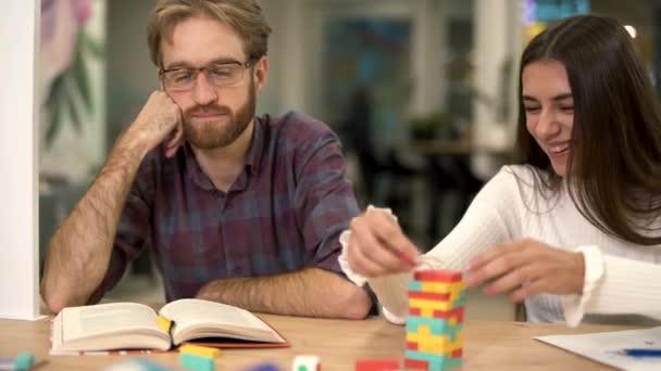 Skupina přátel hraje dřevěný blok věž u stolu. Vousatý muž s brýlemi nejprve podotýká a pak se připojí děvče hry a zábavu.