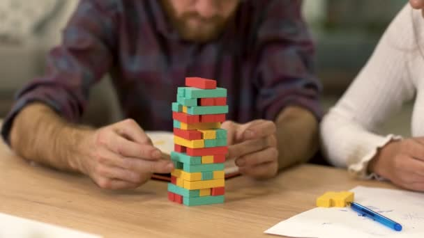 Two collegues after hard working day have a rest and play wooden blocks  tower one by one, discussing their plans and strategy