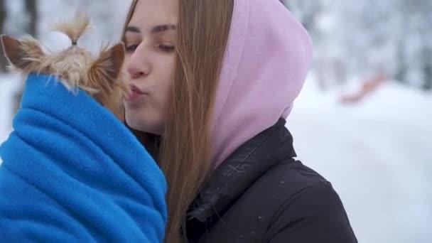 Mladá dívka se Jorkšírský teriér v zimě sněhem pokrytých parku drží psa zabalená v modré deky