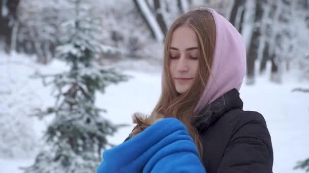 Portrét roztomilá mladá dívka držící Jorkšírský teriér zabalené v modrý ručník na ruce v zimě sněhem pokrytých parku. V pubertě a pet na procházku venku. Zpomalený pohyb