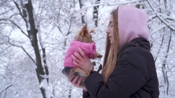Portrét roztomilá mladá dívka s dlouhými vlasy líbání Jorkšírský teriér oblečený v vlny svetr držení psa na ruce v zimě sněhem pokrytých parku. Teenager a psa na procházku venku. Zpomalený pohyb