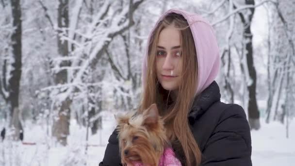 Portrét opuštěné dospívající dívka s dlouhými vlasy objímání Jorkšírský teriér oblečený v vlny svetr držení psa na ruce v zimě sněhem pokrytých parku. Teenager a psa na procházku venku. Sněží