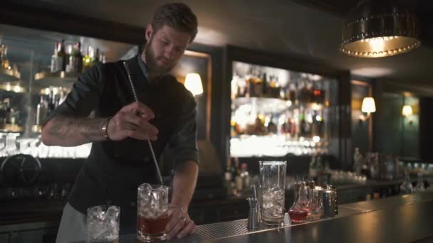 Attractive bearded bartender mixing rum and ice in the glass with long metal stick. Barman making cocktail in modern bar with many bottles on shelves