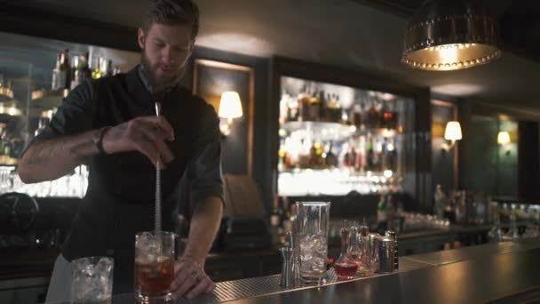 Professional bearded bartender mixing rum and ice in the glass with long metal stick. Barman making cocktail in modern bar with many bottles on shelves