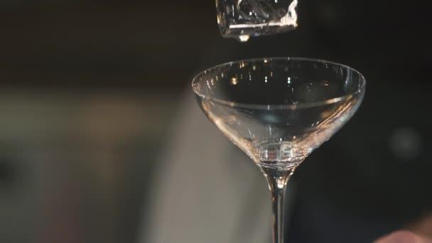 Eiswürfel, der in eine Cocktailglasnahaufnahme fällt. Zeitlupe.
