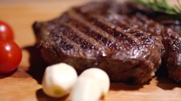 Sůl je pokropil na opečený steak chutné leží na kuchyňské desce s šťavnatých červených rajčat a cibule. Detail.