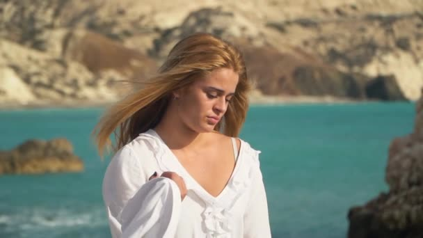 Portrain of young beautiful blond woman at stunning sea view holding mans white shirt in hands. Slow motion.