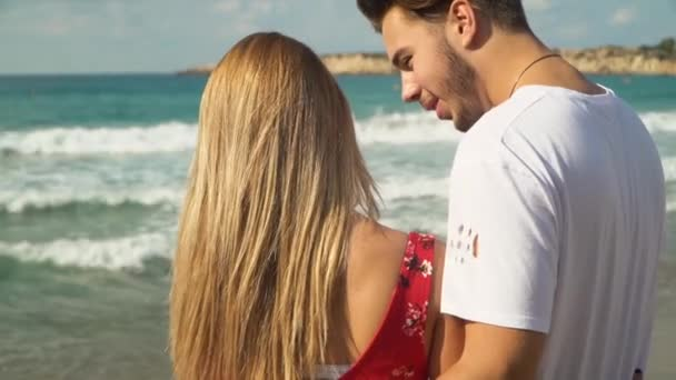 Back view of beautiful young couple hugging together and talking on the beach, view is amazing.