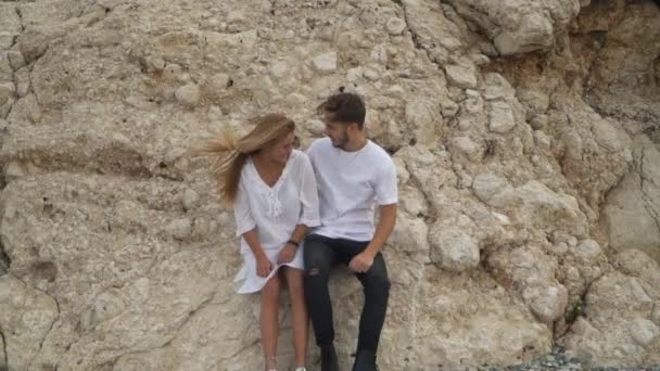 Happy couple sitting on a rock, looking at each other. Man and woman in white shirts spend time outdoors in quiet private place. Top view, shooting from drone