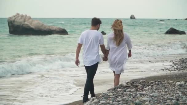 Back view of beautiful young couple holding hands on the beach and walking on stones. Sea waves splashing. Amazing view. Slow motion.