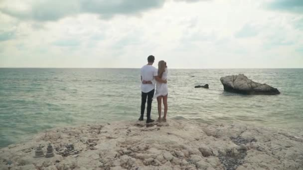 Young couple standing at the sea cost admiring beautiful seascape. Man and woman cuddle each other. Leisure of young family. Shooting from the back