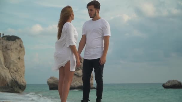 Young couple standing at the rocky sea coast talking in slow motion. Man and woman hold each other hands. Leisure of young family. Shooting from the bottom