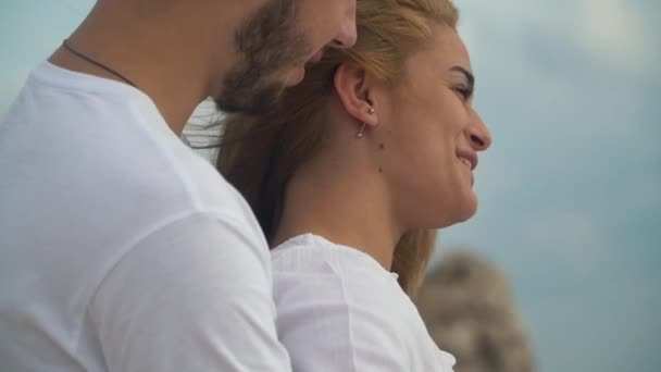 Young man hug from behind a beautiful blond woman and they are happy talking