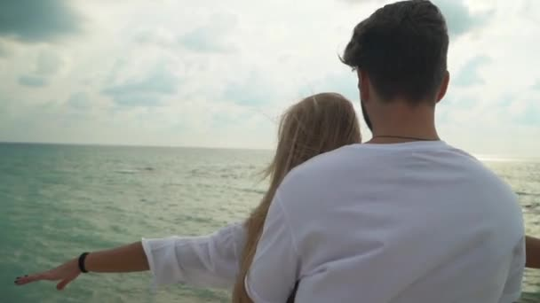 Young couple in white dress standing at the beach close up. Man cuddling woman from behind, lady raising her hands in sides. Lovers have a date at the sea shore. Slow motion.