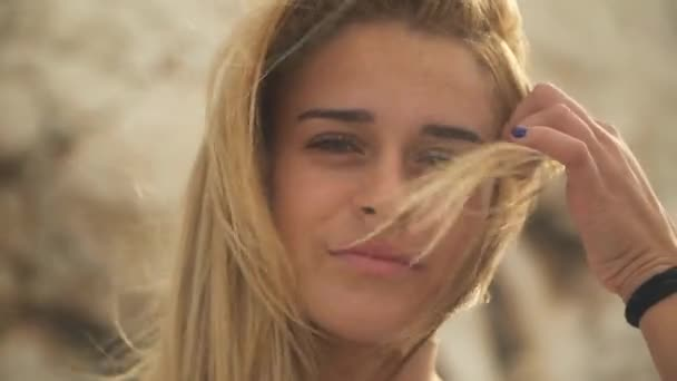Close up portrait of young beautiful woman with amazing blond hair in the wind. The girl looks into the camera while straightening her hair.