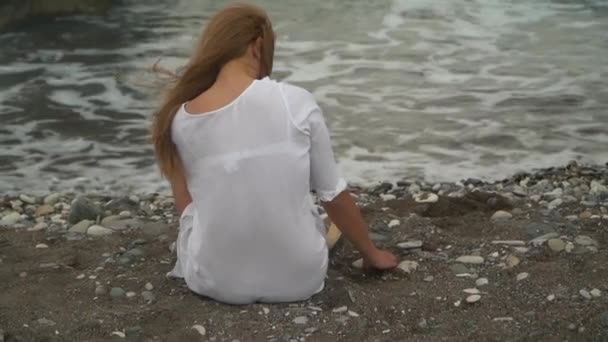 Back view of young woman sitting on the beach, playing with sand near the sea