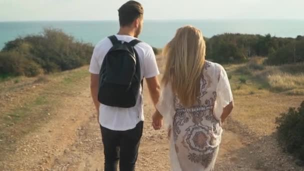 Young beautiful couple walking on the sand road near the sea side and holding hands
