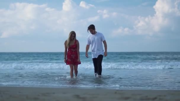 Young beautiful couple walking from the sea in wet cloth