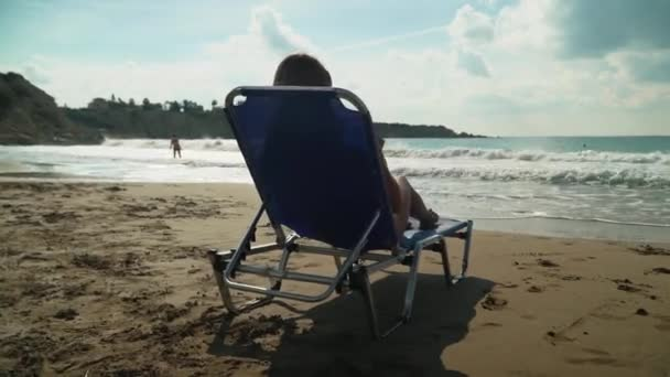 Blond woman sunbathing at the beach lying on deck chair, sea is close near. Girl in sunglasses admires beautiful seascape. Leisure of young woman. Camera moves around