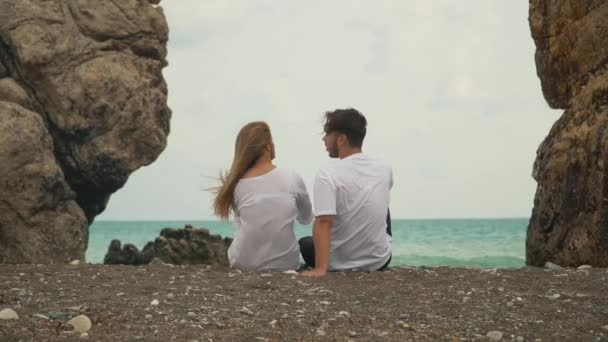 Young couple sit next to each other on the beautiful beach between two rocks and talking