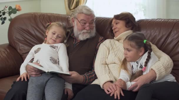 Happy gray-haired bearded grandfather and sweet grandmother reading a book with fairytale to their granddaughters