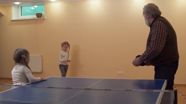 Vnučka dává její dědeček míč poblíž stolnímu tenisu a chystá se udělat první ránu. Zpomalený pohyb