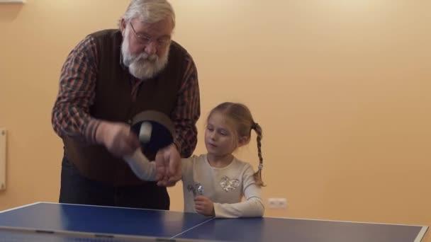 Dědeček učit jeho vnučka hrát stolní tenis. Malá holka honí míč. Volný čas šťastná rodina