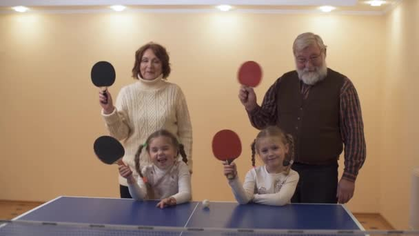 Prarodiče v herně poblíž tenisový stůl se dvěma malé vnučky, všechny mával rakety, pak vlny ruce. Jedna dívka grimas. Volný čas šťastná rodina