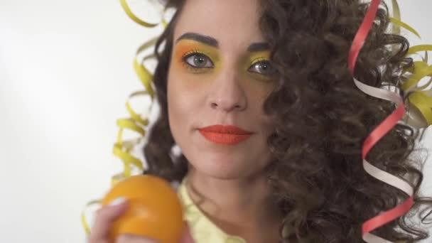 Közelről portré fiatal játékos mosolygó lány világos hogy ki tartja a narancs. Lassú mozgás.