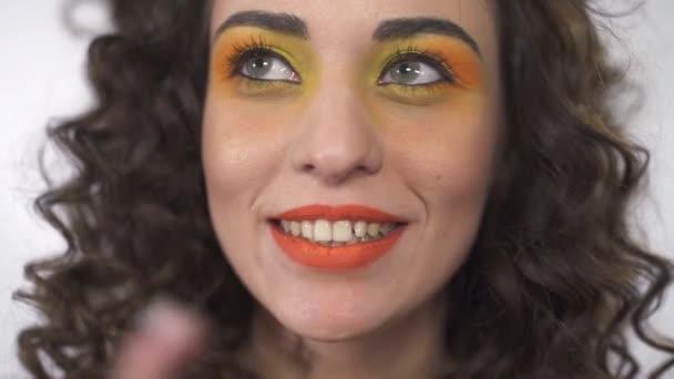 Egy vidám mosolygós lány göndör haj, és ragyogó smink állt egy fehér háttér a stúdióban portré.
