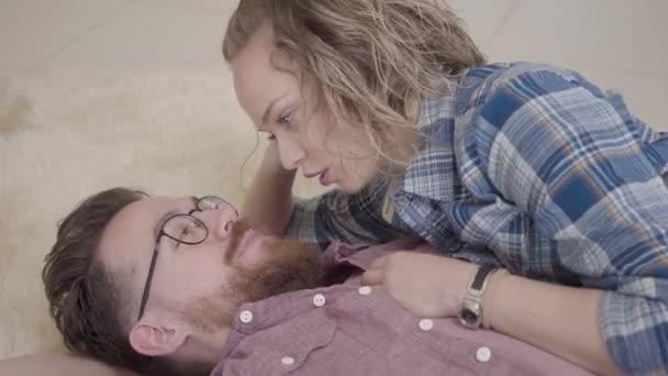 Közelről portréja a férfi és a nő feküdt össze bolyhos szőnyeg, és beszélt. Szakállas férfi szemüveg és szép nő, göndör haj időt együtt otthon