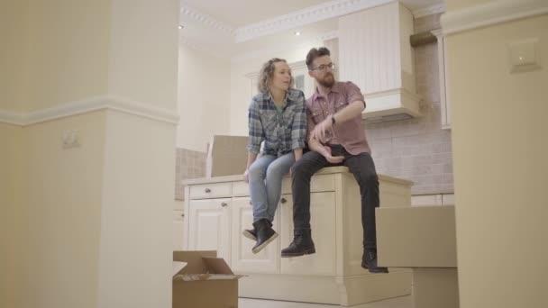 Portrét šťastný mladý pár sedící na kuchyňském stole v novém bytě projednání dispozice domu. Rodina se stěhuje do nového domova.