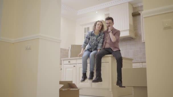 Šťastný mladý pár sedící na kuchyňském stole v novém bytě projednání dispozice domu. Rodina se stěhuje do nového domova.