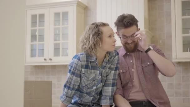 Gioiosa giovane coppia che si siede sul tavolo della cucina in un appartamento nuovo, discutendo il layout della casa. Famiglia si trasferisce in una nuova casa