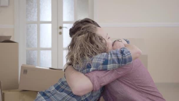 Die junge Familie umarmt sich in einem hellen Raum, im Hintergrund stehen Kisten. Mann und Frau lachen zusammen. Ehepaar zieht in ein neues Zuhause
