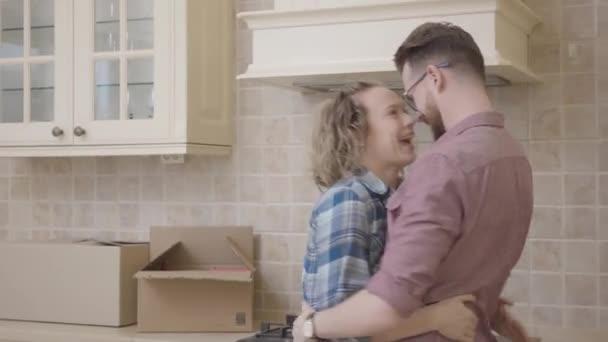 Radostné mladá rodina zahrnující v kuchyni v jejich novém domově. Šťastný pár přestěhoval do nového bytu.