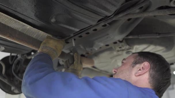 Zkušený mechanik auto v modré uniformě stojící pod auto s klíčem a utahování šroubů v čerpací stanici.