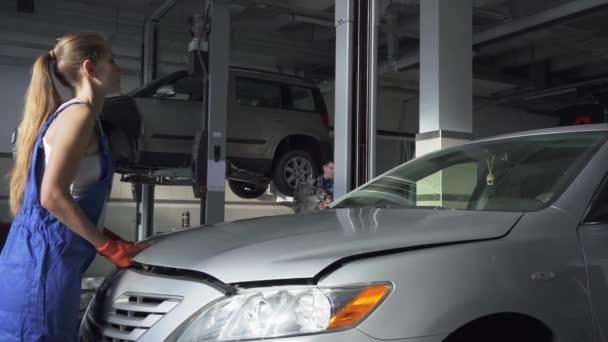 Samice mladé auto specialista otevírací kapotu auta pro opravy nebo kontrolu v autoservis. Auto servis, opravy, údržbu a lidé koncept - mechanik žena pracující v dílně.