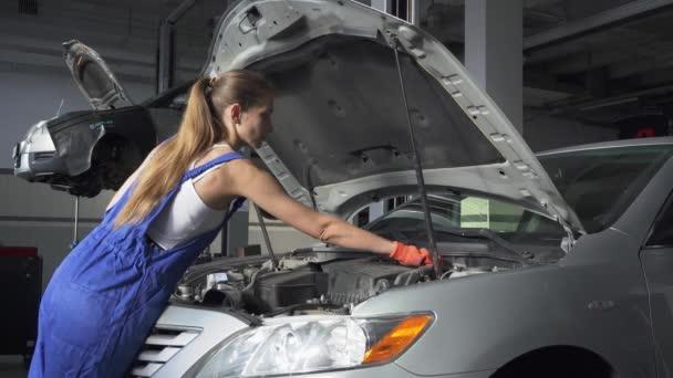 Gyönyörű lány egységes bezárja a motorháztető az autó állt a jármű a benzinkút előtt. Autó-szerviz, javítás, karbantartás és emberek fogalma - szerelő nő dolgozik a műhelyben.