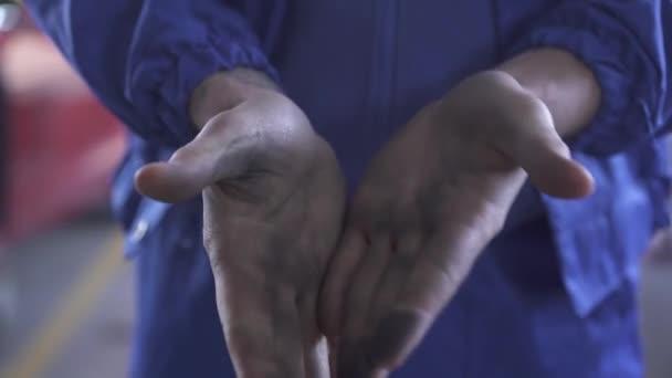 Nerozpoznaný Automechanika ukazuje jeho špinavé ruce po opravě automobilu v čerpací stanici. Closeup