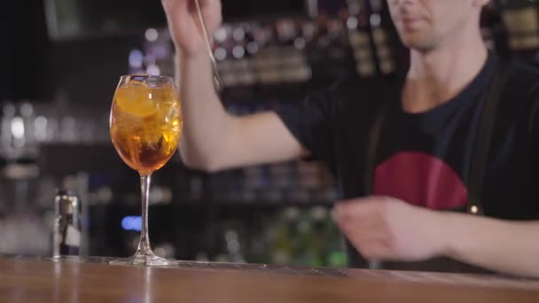 Young bartender mixing a refreshing whiskey or alcohol cocktail in glass with ice. Close up.