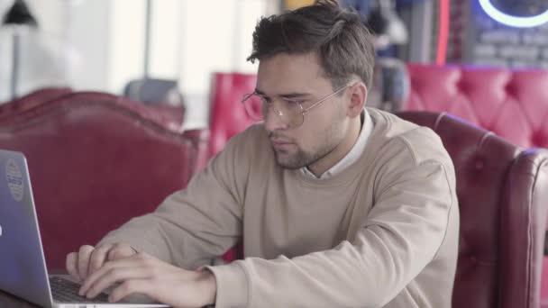 Pohledný muž pracující s přenosným počítačem v moderní kavárně zblízka. Stylový jistý podnikatel přesune jeho tělo v rytmu hudby. Pozitivní na volné noze pracuje na projektu