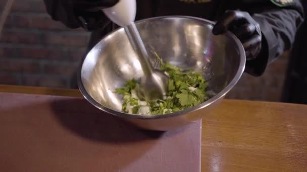 Rukou šéfkuchaře v černé gumové rukavice cook šlehačky s petrželkou pomocí mixéru velké hliníkové mísy zblízka. Příprava omáčky v moderní restauraci
