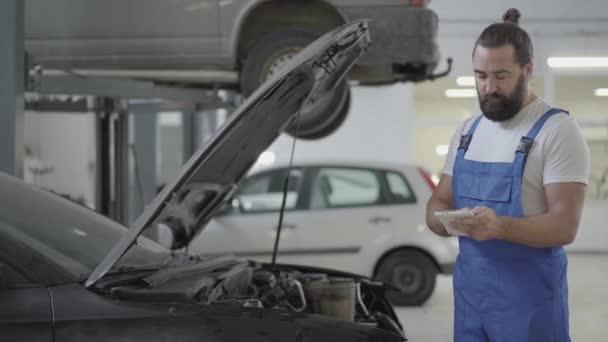 Der erwachsene Mechaniker steht mit offener Motorhaube neben dem Auto und überprüft die Informationen auf seinem Handy. Bärtiger Mann in Uniform repariert Auto in Autowerkstatt