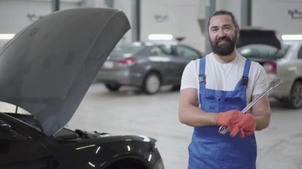 Pro dospělé mechanik stál vedle auta s otevřenou kapotou a v rukou držel obrovská vyškubnout. Vousatý muž v uniformě, oprava automobilů v auto opravy stanice