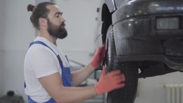 Vousatý mechanik kontrola odpružení nebo brzd v kola automobilu zdvižené automobilu v servisním centru. Obratný muž v uniformě, oprava aut